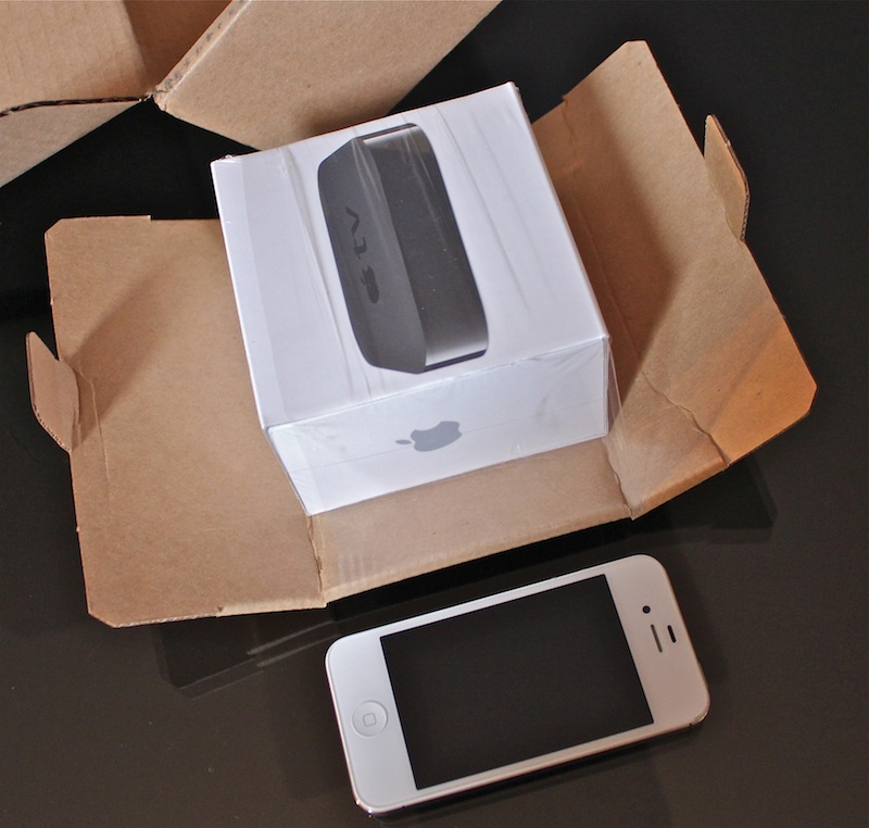 apple tv box. inside the box is an ac power cable (the unit contains its own supply), apple remote, introductory booklet, and small black device itself, tv